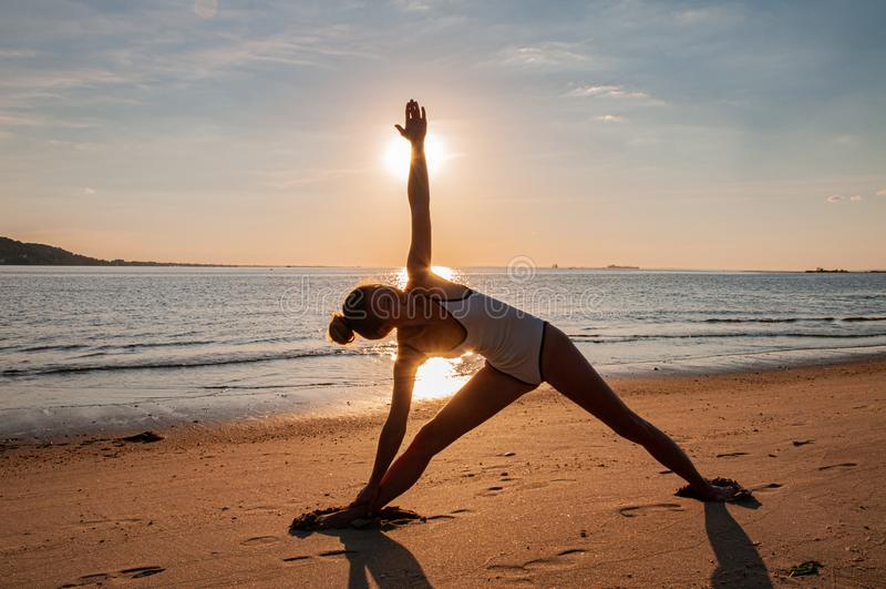 Silhouet van yogavrouw op het strand bij zonsopgang De vrouw oefent yoga bij zonsondergang op overzeese kust uit stock foto's