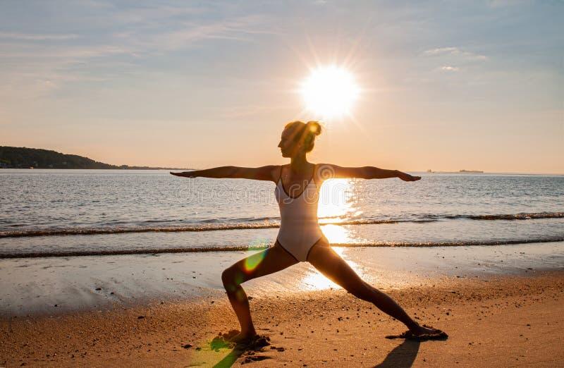 Silhouet van yogavrouw op het strand bij zonsopgang De vrouw oefent yoga bij zonsondergang op overzeese kust uit royalty-vrije stock foto