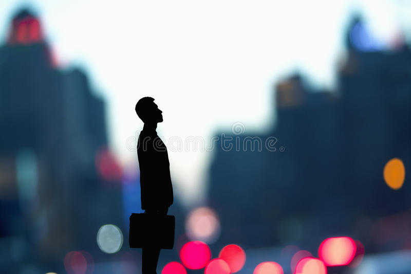 Silhouet van zakenman die een aktentas met vage stadslichten houden achter hem stock foto