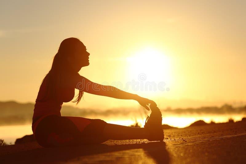 Silhouet van zich geschiktheidsvrouw het uitrekken bij zonsondergang royalty-vrije stock afbeelding