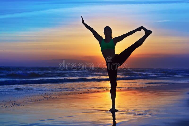 Silhouet van zich vrouw het uitrekken bij yogaterugtocht op zonsondergangstrand stock foto
