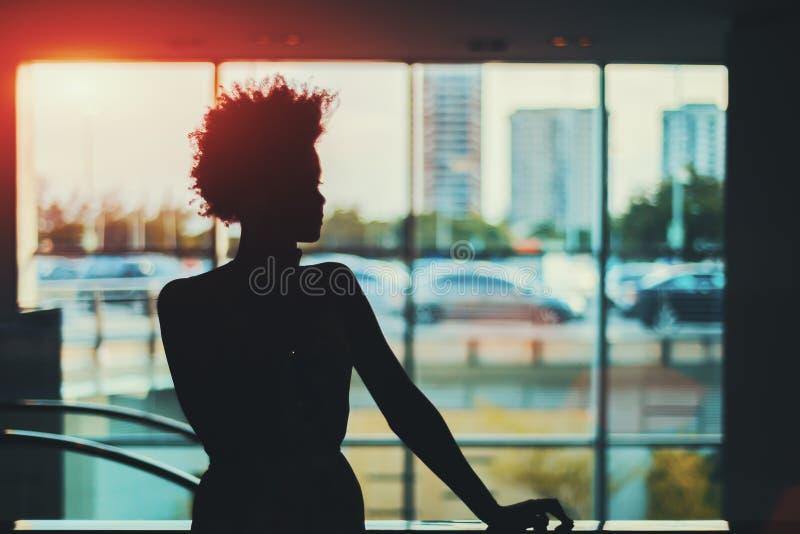 Silhouet van zwart krullend meisje voor venster royalty-vrije stock fotografie
