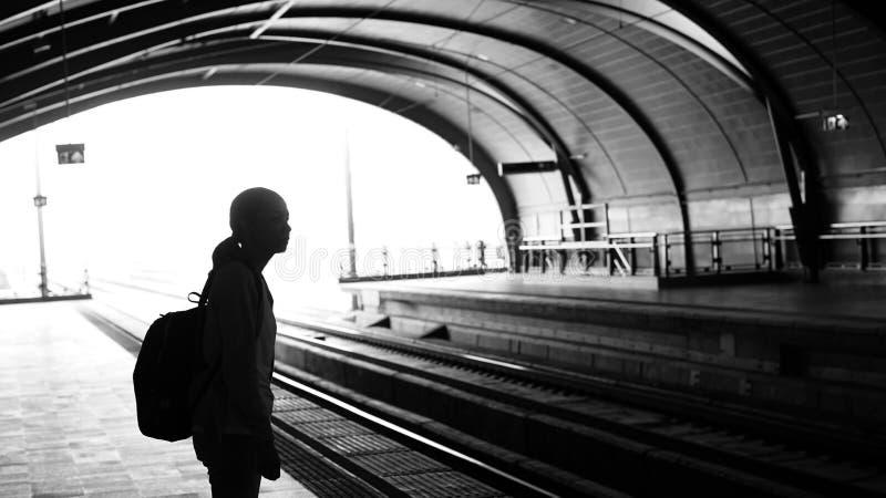 Silhouet voor toeristenmeisje die backpacker op trein bij wachten stock fotografie