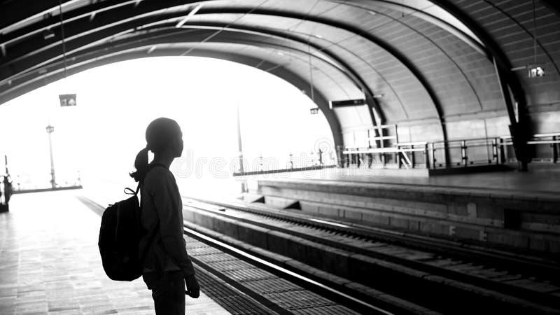 Silhouet voor toeristenmeisje die backpacker op trein bij wachten royalty-vrije stock foto's