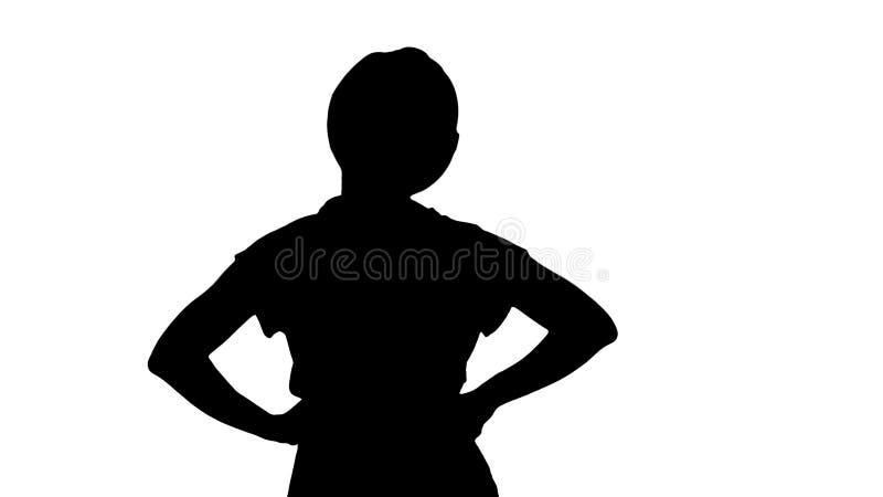 Silhouet Vrouwelijke bouwvakker die met handen op heupen iets bekijken royalty-vrije stock afbeeldingen