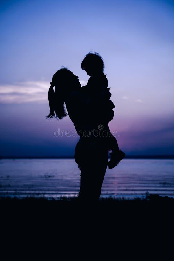 Silhouet zijaanzicht van moeder en kind die bij rivieroever genieten van stock afbeelding