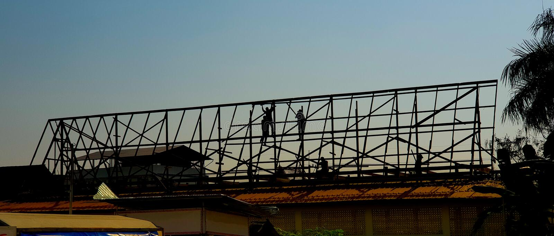 Silhouetarbeiders voor het dakgebouw in bouwwerf stock fotografie