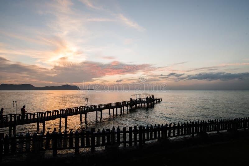 Silhouetbrug en pavillion op het overzees met mensengang op t stock foto's