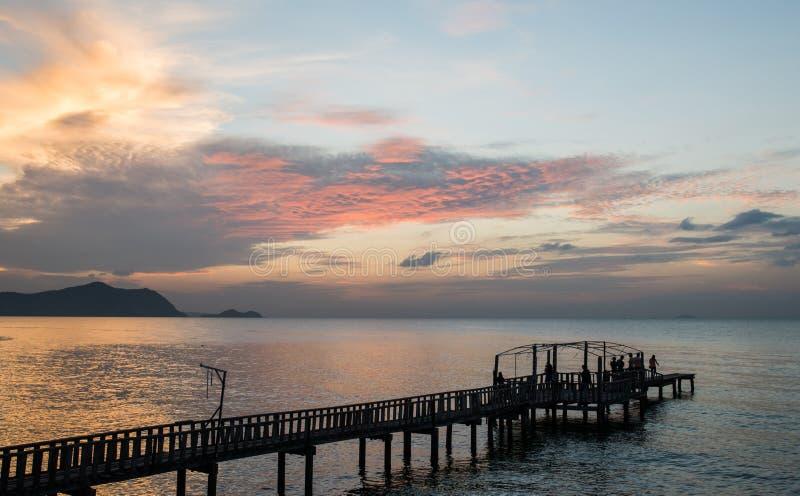 Silhouetbrug en pavillion op het overzees met mensengang op t stock foto