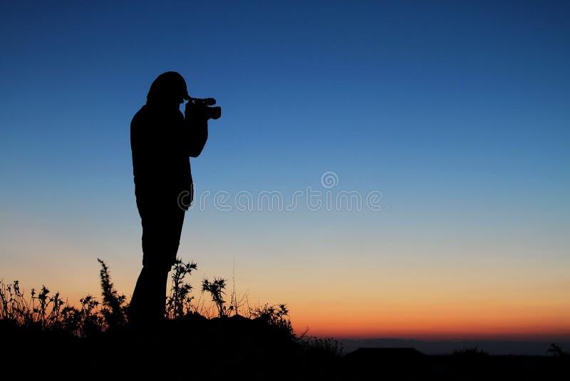 Silhouetcameraman tegen een zonsondergang royalty-vrije stock afbeeldingen