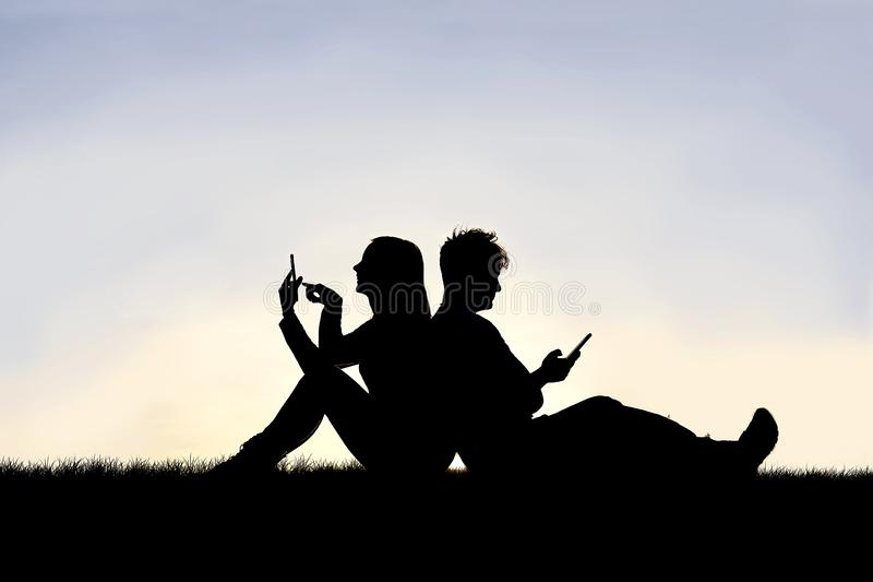 Silhouete della coppia sposata della donna e dell'uomo sta sedendo di nuovo ad a vicenda, lavorando ai loro telefoni cellulari immagine stock libera da diritti