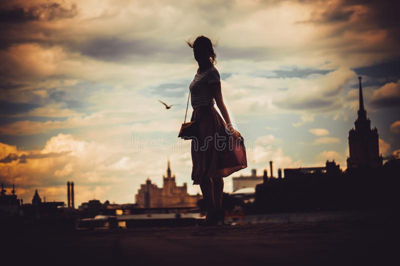 Silhouete of girl in dress standing on the background of skyline stock photo