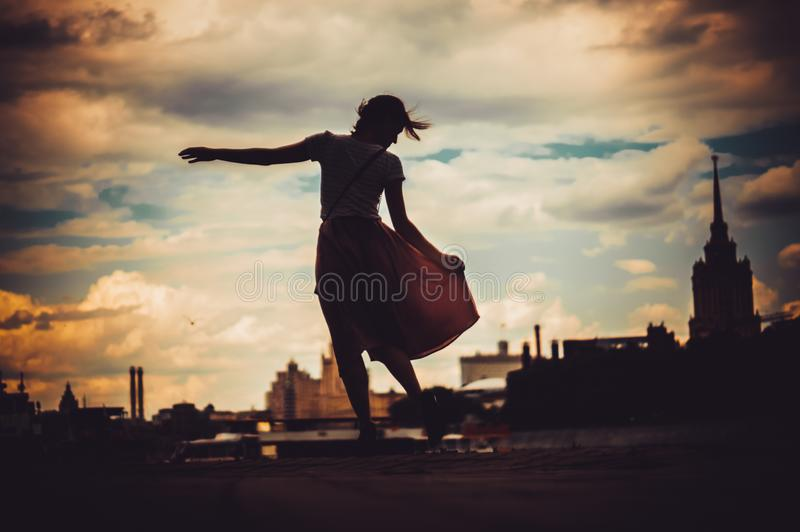 Silhouete of girl in dress standing on the background of skyline royalty free stock images