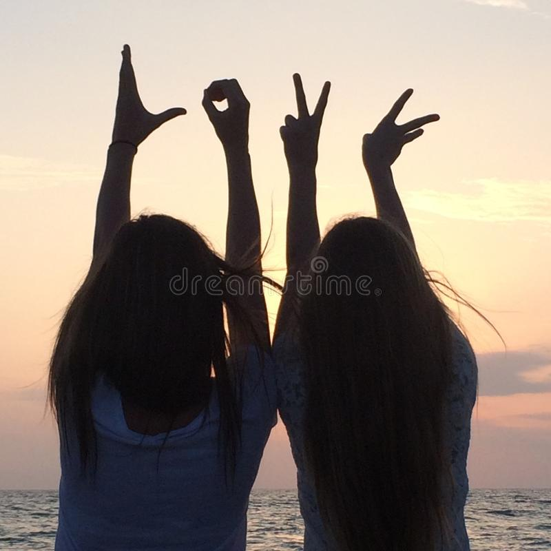 SILHOUETE LOVE SYMBOL. GIRLS MAKING LOVE SIGN WITH HANDS DURING THE SUNSET royalty free stock photo