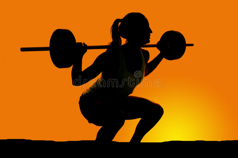 Silhouete of woman deep squat. A silhouette of a woman doing a deep squat with a bar on her back stock photos