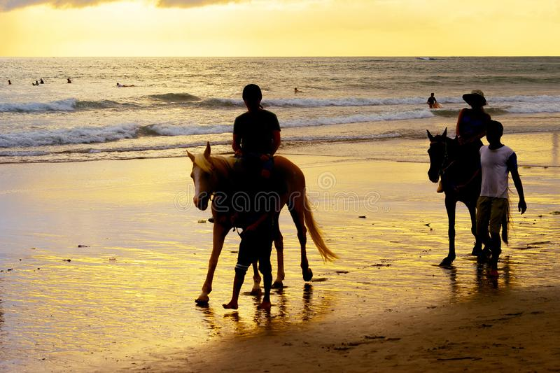 Silhouetes van toeristen die paarden berijden op oceaanstrand bij zonsondergang, Bali, Indonesië royalty-vrije stock foto