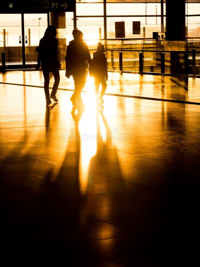 Silhouetfamilie die in luchthaven voor vertrek voorbereidingen treffen stock foto's