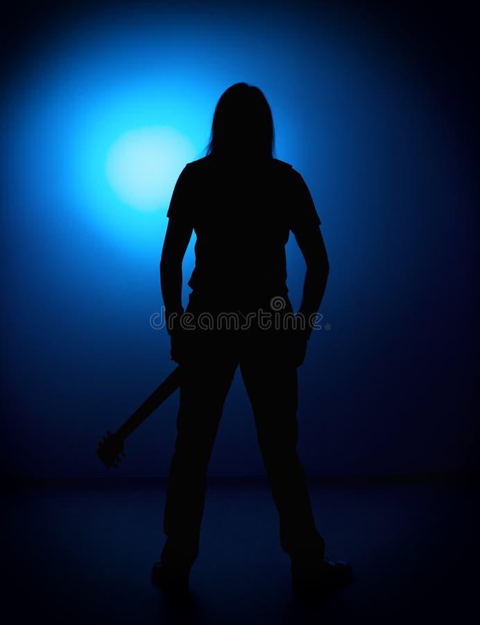 Silhouetgitaristen van een popgroep met gitaar op blauwe achtergrond stock foto