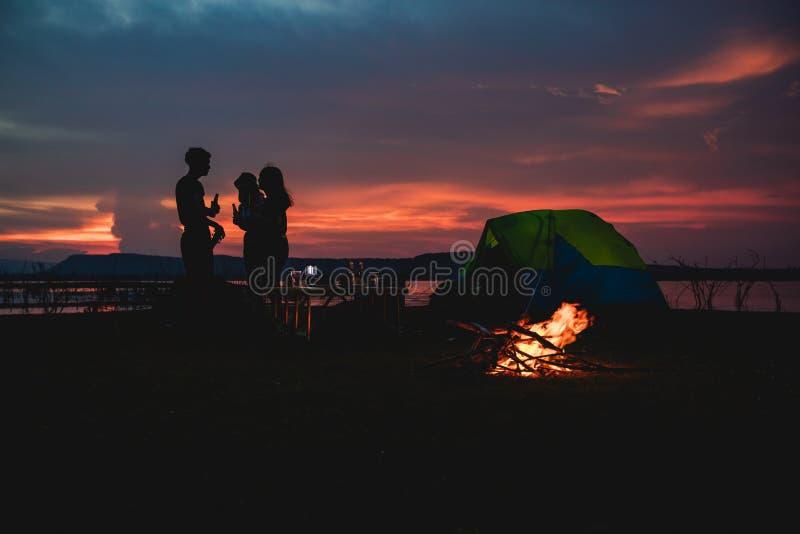 Silhouetgroep het Aziatische vriendentoerist drinken en het spelen gitaar samen met geluk in de Zomer terwijl het hebben van dich stock afbeeldingen
