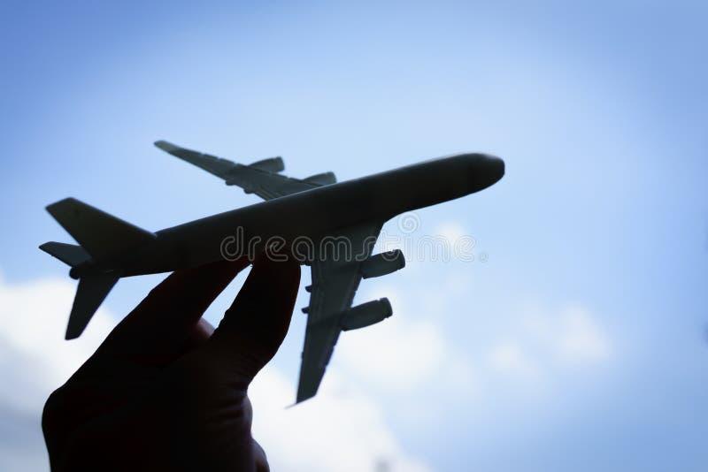silhouethand die een stuk speelgoed vliegtuig met blauwe hemelbackgro houden stock foto