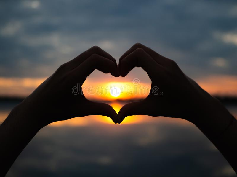 Silhouethanden om hartvorm op zonsondergangachtergrond te zijn Gelukkig, Liefde, de dagidee van Valentine ` s, teken, symbool, co royalty-vrije stock foto