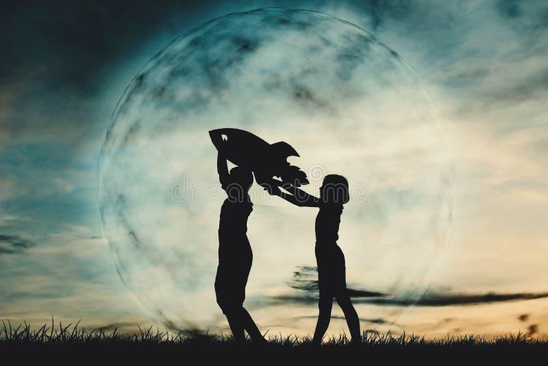 Silhouetjongen en meisje die een raketdocument op de hemel met maanachtergrond houden stock afbeelding