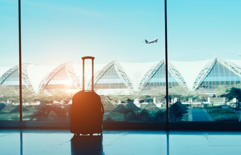 Silhouetkoffer, bagage op zijruit bij luchthaven eind internationaal en vliegtuig buiten op vliegvlucht in de blauwe hemel RT stock fotografie