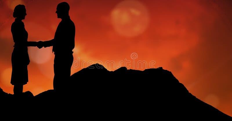 Silhouetmedewerkers die handen op bergen schudden tijdens zonsondergang royalty-vrije stock afbeelding