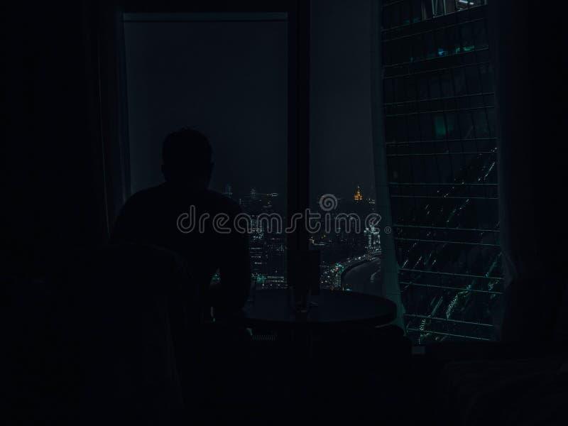 Silhouetmens die aan mooie kleur van het licht van de stadsnacht van modern wolkenkrabbervenster nacht bekijken stock afbeeldingen