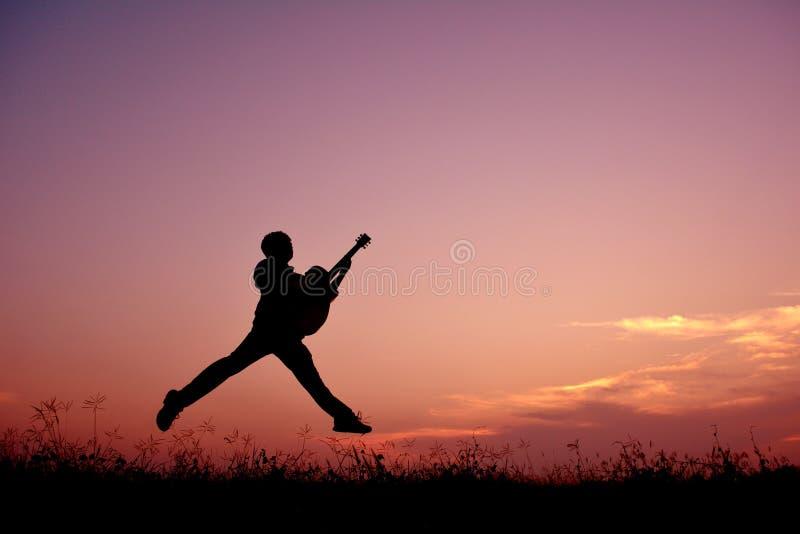 Silhouetmens die met gitaar springen royalty-vrije stock fotografie