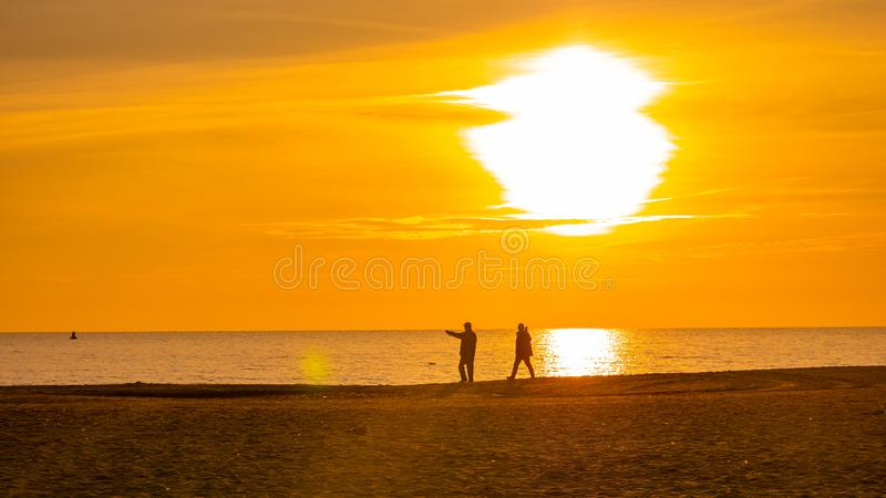 Silhouetmens die op het strand bij zonsondergang of zonsopgang lopen stock foto's