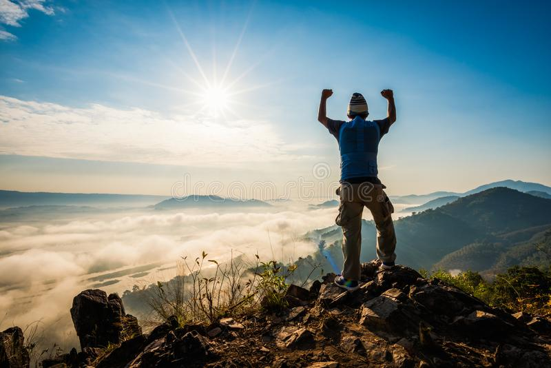 Silhouetmens die zich bovenop de berg bevinden die op de zonstijging met mist letten stock afbeeldingen