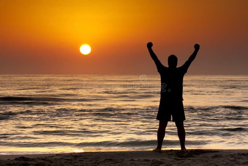Silhouetmens het Toenemen Wapens Overzeese Zon Triumph stock foto's