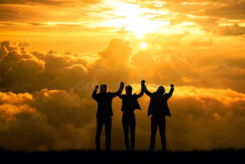 Silhouetmensen die concepten commerciële de teammens en vrouw met wapens omhoog in de lucht voor het concept van het succesdoel w stock foto