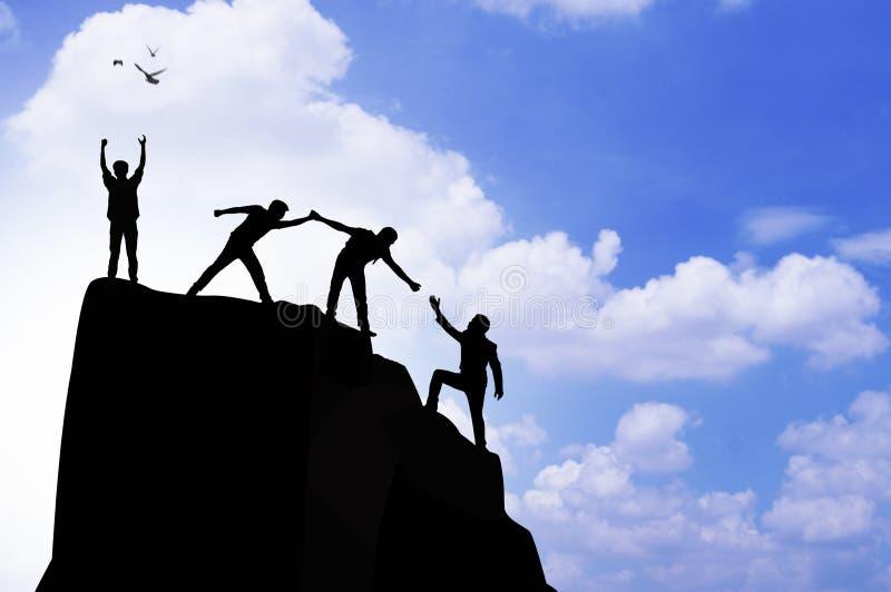 silhouetmensen die hand helpen te beklimmen royalty-vrije stock afbeelding