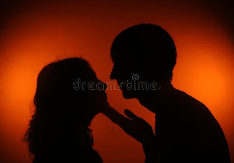 Silhouetpaar die elkaar kijken stock foto's