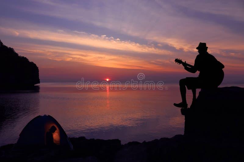 Silhouetpaar die en een gitaar op het strand spelen kamperen royalty-vrije stock afbeeldingen
