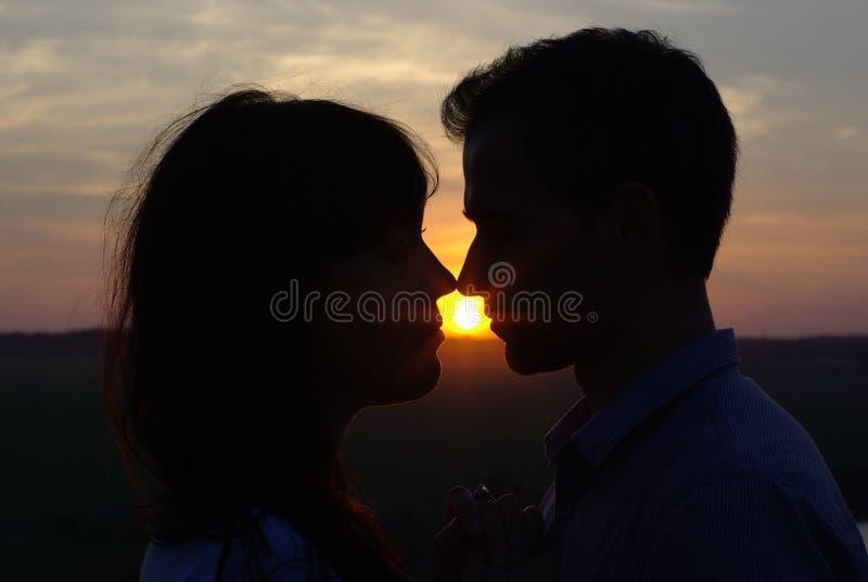 Silhouetpaar het kussen bij zonsondergang royalty-vrije stock foto's