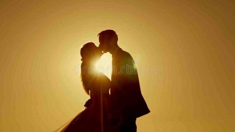 Silhouetpaar het kussen over zonsondergangachtergrond royalty-vrije stock foto's
