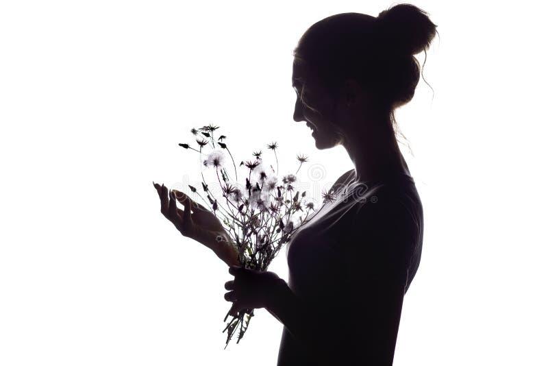 Silhouetportret van een mooi meisje met een boeket van droge paardebloemen, het gezichtsprofiel van een dromerige jonge vrouw op  stock afbeeldingen