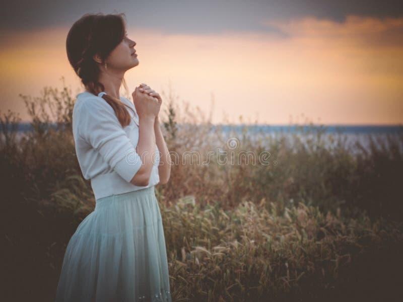 Silhouetprofiel van een mooi meisje in een kleding die aan God op het gebied, een jonge vrouw bidden die op aard tijdens zonsonde stock foto's