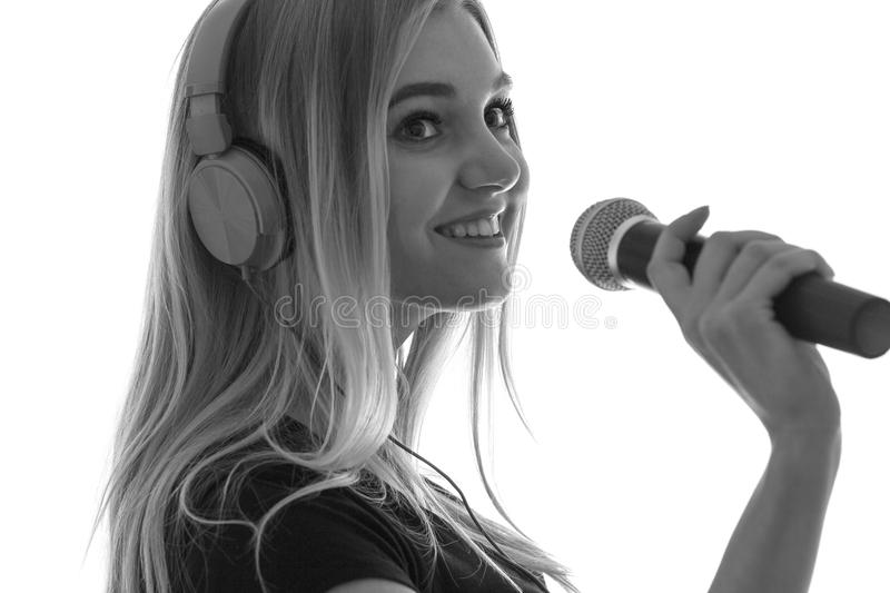 Silhouett of a young woman in headphones and with microphone royalty free stock image