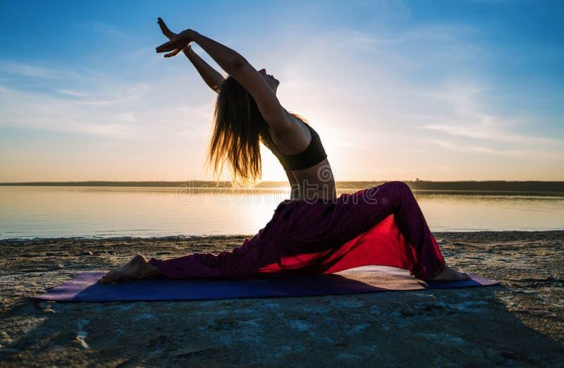Silhouette женщина йоги на пляже на заходе солнца стоковое изображение