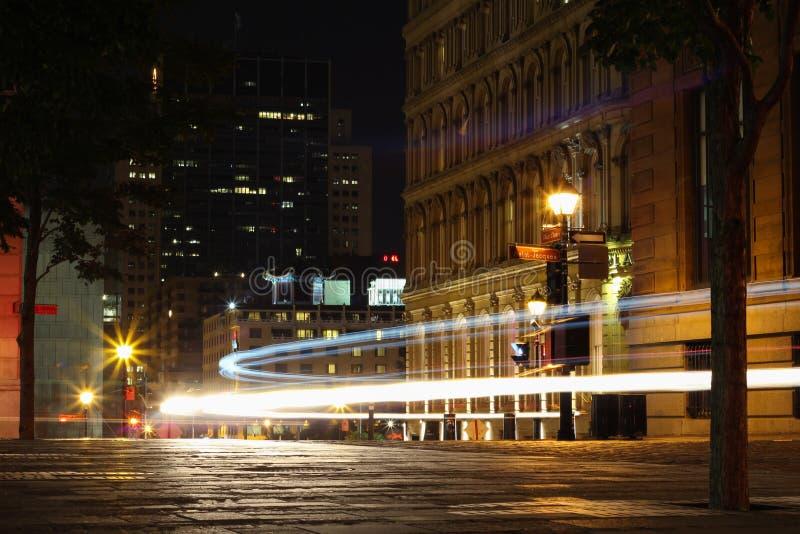 Silhouette автомобили с красными задним светом и светофорами в Монреале стоковые фото