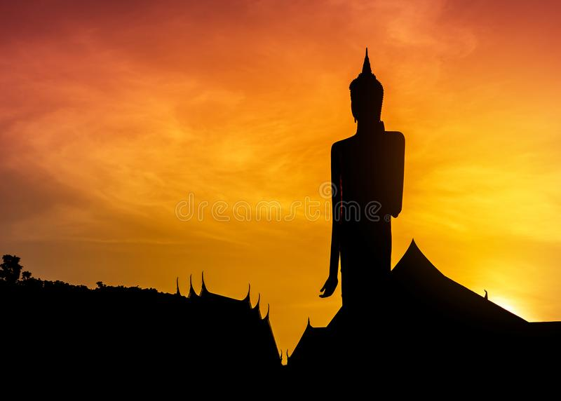 Silhouette большая статуя Будды стоя в тайском виске на заходе солнца стоковые фото