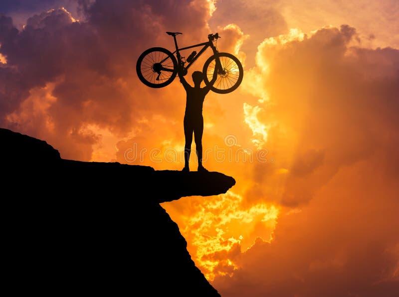 Silhouette велосипед горы человека поднимаясь над его головой na górze горы скалы с заходом солнца стоковые фотографии rf