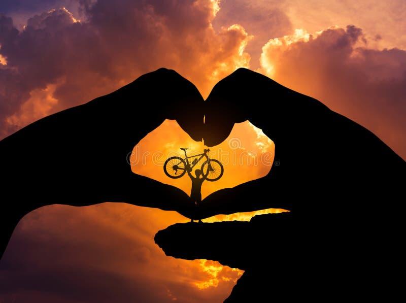 Silhouette велосипед стойки человека поднимаясь в форме сердца рук стоковое изображение rf