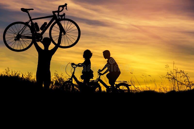 Silhouette велосипед стойки человека поднимаясь над его головой с велосипедом катания мальчика и маленькой девочки на заходе солн стоковые фотографии rf