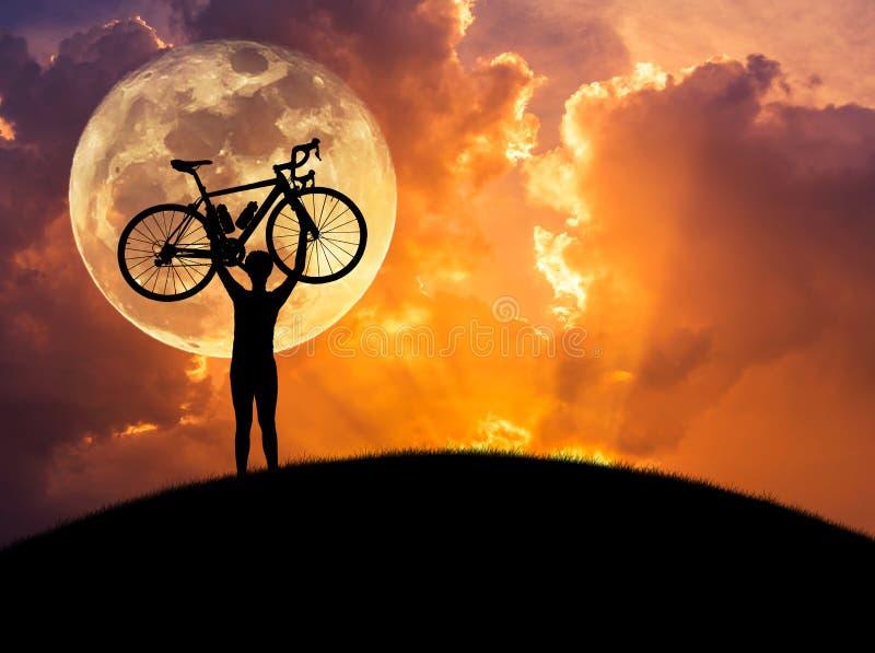 Silhouette велосипед человека поднимаясь над его головой в заходе солнца с полнолунием стоковые фото