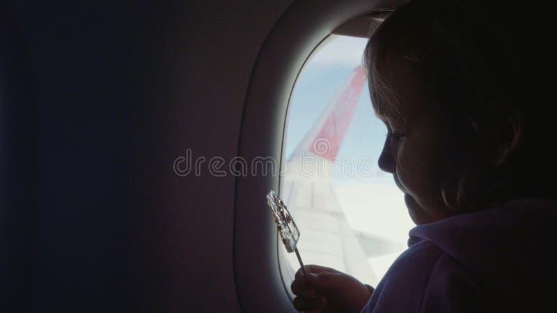 Silhouette девушка ребенка всасывая помадки на деревянной ручке над иллюминатором в самолете стоковое фото rf